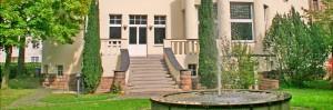 Außenansicht Eingangsbereich der Akademie im Leben mit Garten und Springbrunnen