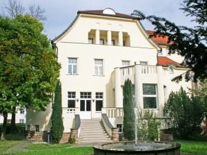Außenansicht Gebäude Akademie im Leben mit Garten und Springbrunnen