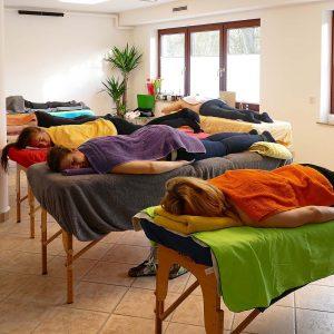 Seminargruppe entspannt nach einer Behandlung auf Liegen