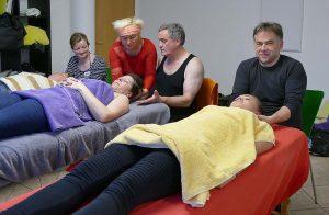 Heilpraktikerin mit Seminargruppe bei einer praktischen Übung zum Thema Nackenmuskulatur und Rücken