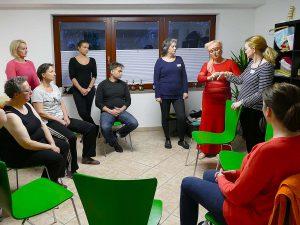 Heilpraktikerin mit Seminargruppe bei der Erklärung und Vorführung zum Thema Handgelenk